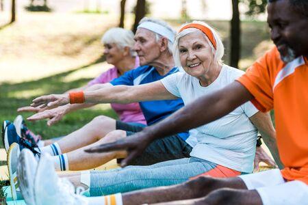 Selektiver Fokus multikultureller Frauen und Männer im Ruhestand in Sportbekleidung, die auf Fitnessmatten trainieren