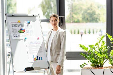 confident businesswoman in formal wear standing near flipchart with infographic in office Foto de archivo
