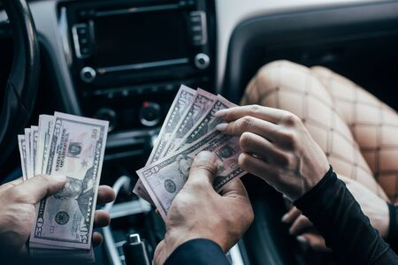 cropped view of client paying dollar banknotes to woman in car Stock fotó