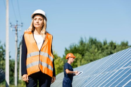 attractive businesswoman in hardhat and safety vest looking away
