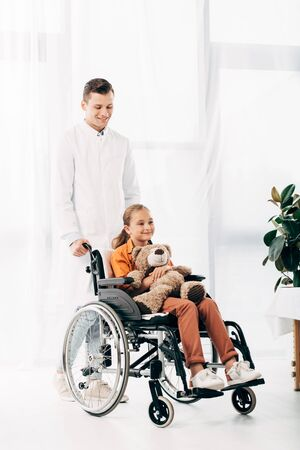 full length view of pediatrist in white coat and kid with teddy bear on wheelchair