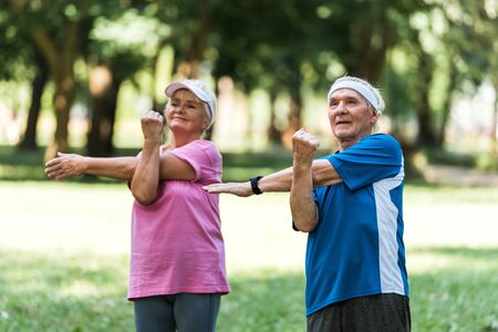 happy retired couple doing exercises while standing in park Stock Photo
