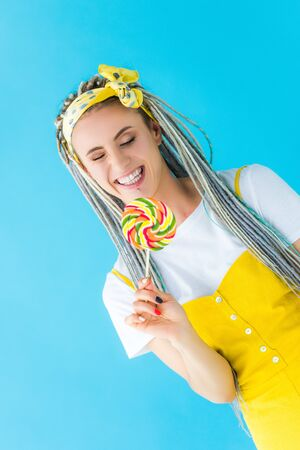 smiling girl with dreadlocks holding lollipop isolated on turquoise