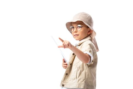 pensive explorer child in glasses and hat holding digital tablet and pointing with finger isolated on white Banco de Imagens - 130117296