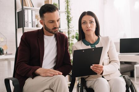 disabled businesswoman holding clipboard and looking at camera while sitting near business partner in office Stock Photo