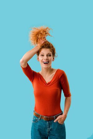 young excited woman holding red curly hair isolated on blue