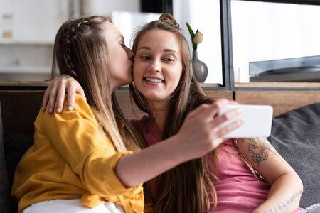 lesbian in yellow blouse kissing girlfriend while taking selfie Archivio Fotografico