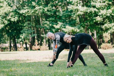mature sportsman and sportswoman smiling at camera while training in park together Stockfoto