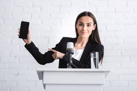 smiling lecturer standing on podium tribune and pointing with finger at smartphone with blank screen Reklamní fotografie