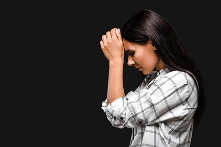 side view of upset young woman touching head isolated on black
