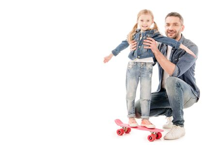 smiling father and daughter on skateboard isolated on white