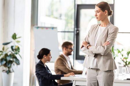 pensive businesswoman in formal wear standing with crossed arms in office Foto de archivo