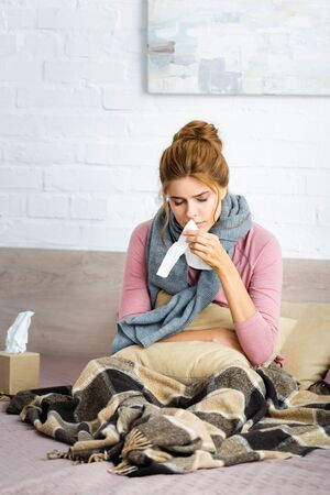 attractive and ill woman with grey scarf sitting in bed and holding napkin