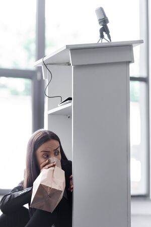 frightened lecturer breathing into paper bag while sitting on floor in conference hall and suffering from panic attack Reklamní fotografie