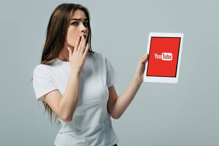 KYIV, UKRAINE - JUNE 6, 2019: shocked beautiful girl in white t-shirt showing digital tablet with youtube app isolated on grey Editorial