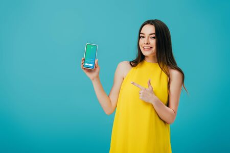 KYIV, UKRAINE - JUNE 6, 2019: happy beautiful girl in yellow dress pointing with finger at smartphone with twitter app isolated on turquoise Editorial