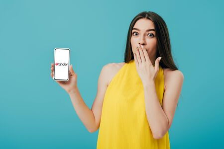 KYIV, UKRAINE - JUNE 6, 2019: shocked beautiful girl in yellow dress showing smartphone with tinder app isolated on turquoise