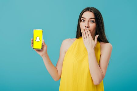 KYIV, UKRAINE - JUNE 6, 2019: shocked beautiful girl in yellow dress showing smartphone with Snapchat app isolated on turquoise
