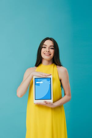 KYIV, UKRAINE - JUNE 6, 2019: smiling beautiful girl in yellow dress showing digital tablet with twitter app isolated on turquoise