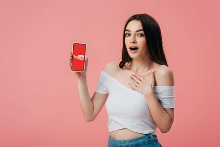 KYIV, UKRAINE - JUNE 6, 2019: beautiful shocked girl holding smartphone with youtube app isolated on pink