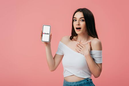 KYIV, UKRAINE - JUNE 6, 2019: beautiful shocked girl holding smartphone with tinder app isolated on pink