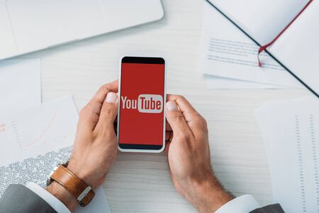top view of man holding smartphone with youtube app