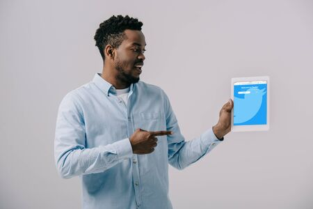 happy african american man pointing with finger at digital tablet with twitter app on screen isolated on grey