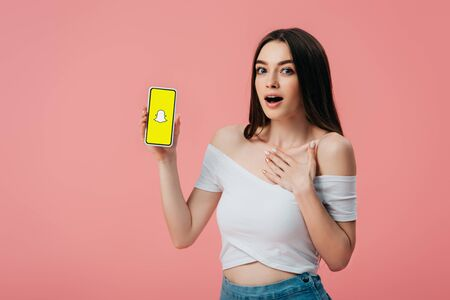 KYIV, UKRAINE - JUNE 6, 2019: beautiful shocked girl holding smartphone with snapchat app isolated on pink