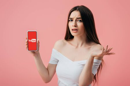 KYIV, UKRAINE - JUNE 6, 2019: beautiful confused girl holding smartphone with youtube app and showing shrug gesture isolated on pink