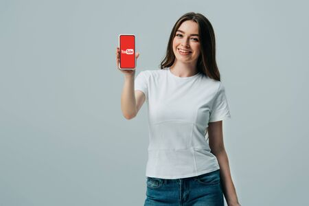 KYIV, UKRAINE - JUNE 6, 2019: happy beautiful girl in white t-shirt showing smartphone with youtube app isolated on grey