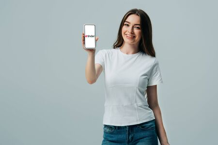 KYIV, UKRAINE - JUNE 6, 2019: happy beautiful girl in white t-shirt showing smartphone with tinder app isolated on grey