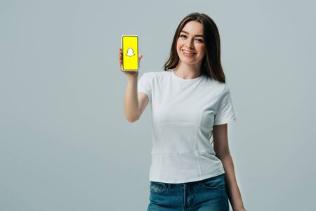 KYIV, UKRAINE - JUNE 6, 2019: happy beautiful girl in white t-shirt showing smartphone with snapchat app isolated on grey