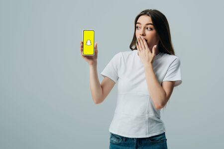KYIV, UKRAINE - JUNE 6, 2019: shocked beautiful girl in white t-shirt showing smartphone with Snapchat app isolated on grey