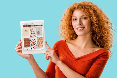 KYIV, UKRAINE - JULY 16, 2019: smiling redhead woman holding digital tablet with pinterest app, isolated on blue