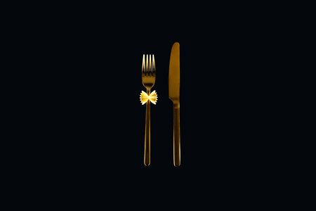 uncooked farfalle pasta on metal fork near knife isolated on black