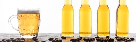 panoramic shot of bottles and mug of light beer near coffee beans isolated on white