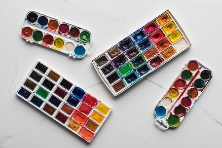 top view of colorful paint palettes on marble white surface 版權商用圖片