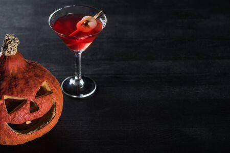 gruseliger Halloween-Kürbis und roter Cocktail auf schwarzem Hintergrund