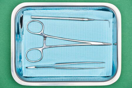 top view of dental tools in metallic plate isolated on green Banco de Imagens