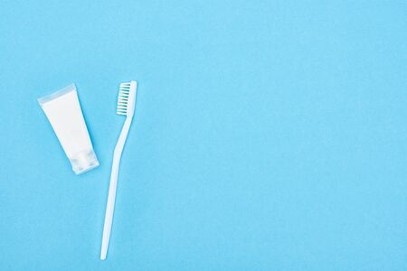 top view of white toothbrush and toothpaste isolated on blue