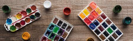 top view of colorful paint palettes on wooden brown table with gouache, panoramic shot