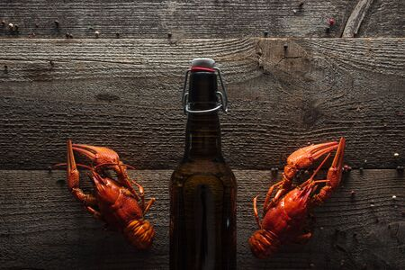 top view of red lobsters and bottle with beer on wooden surface Stock Photo