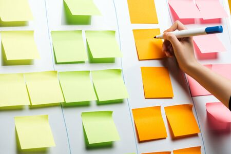 Ausgeschnittene Ansicht der Geschäftsfrau, die auf Aufklebernotizen mit Kopienraum schreibt