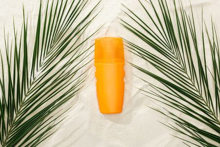top view of palm leaves and orange sunscreen on sand