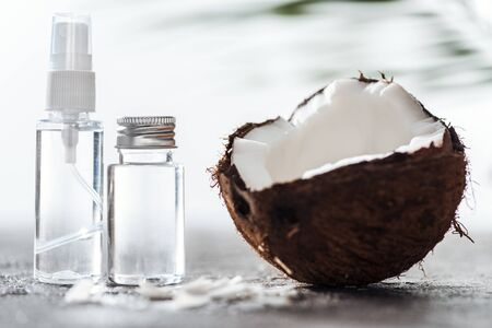 selective focus of bottles with coconut water near cracked coconut and coconut shavings Imagens