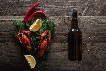 top view of red lobsters, lemon slices, dill, pepper and bottle with beer on wooden surface