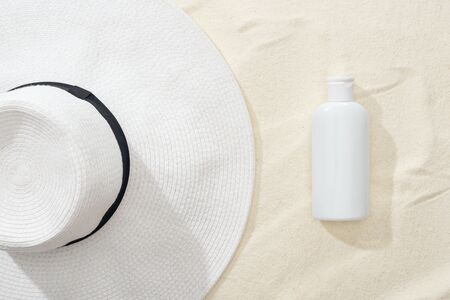 top view of white sunscreen lotion and straw hat on sand