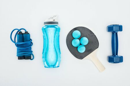 top view of sport bottle near ping pong balls and sport equipment isolated on white