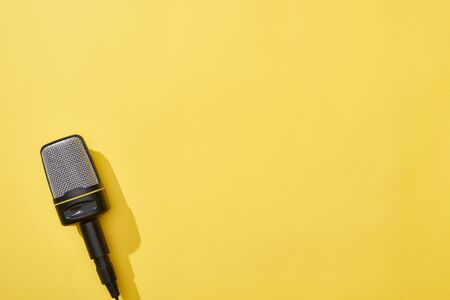 top view of microphone on yellow background with copy space