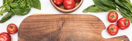 panoramic shot of wooden chopping board, greenery and cherry tomatoes